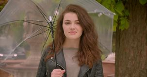 Portrait of cute of caucasian brunette model spinning the umbrella watching seductively into camera in the green park. Portrait of cute of caucasian brunette stock footage