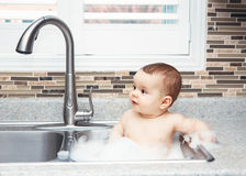 Portrait of cute Caucasian funny baby girl boy with dark black eyes sitting in big kitchen sink with water and foam Royalty Free Stock Photos
