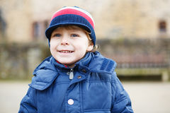 Portrait of cute caucasian toddler boy in warm clothes on cold d Royalty Free Stock Images