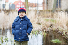 Portrait of cute caucasian toddler boy in warm clothes on cold d Stock Photo