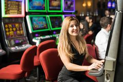 Cute woman in a casino. Portrait of a cute Caucasian young women playing in a slot machine at a casino and smiling Stock Photo
