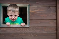 Cheeky boy looking through the window. Portrait of a cute cheeky little Caucasian boy looking through the window of a wooden toy house in a outdoor playground stock images