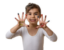 Portrait of a cute cheerful girl showing her painted hands. Funny little girl with hands and fingers painted in colorful paint stock photos