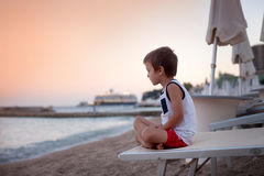 Portrait of cute child, boy, contemplating the beach on sunset Royalty Free Stock Photography