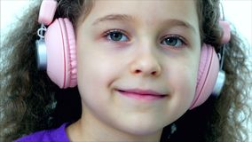 Portrait of a cute child with curly hair, caucasian little girl in a purple t-shirt with a pink headphones listening stock video footage