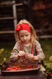 Portrait of cute child girl making rowan berry beads in autumn garden Royalty Free Stock Images
