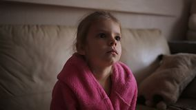 Portrait of a cute child girl sitting on couch and watching TV. At home stock video
