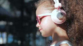 Portrait of a Cute Child, a Wonderful Little Beautiful Girl in a White Dress With Pink Glasses and Pink Headphones stock video footage