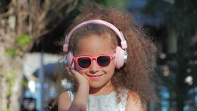 Portrait of a Cute Child, a Wonderful Little Beautiful Girl in a White Dress With Pink Glasses and Pink Headphones stock video