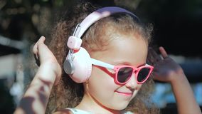 Portrait of a Cute Child, a Wonderful Little Beautiful Girl in a White Dress With Pink Glasses and Pink Headphones stock footage