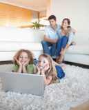 Portrait of cute children using a notebook. While their parents are watching in their living room Stock Photos