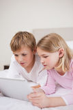 Portrait of cute children using a tablet computer Royalty Free Stock Photography