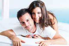 Portrait of cute couple on bed. Stock Image