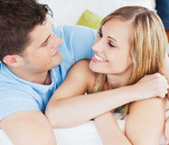 Portrait of a cute couple looking at each other. Relaxing on the sofa at home royalty free stock photography