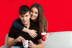 Portrait of cute couple with mugs on sofa. Close up portrait of cute couple drinking coffee together on couch.Isolated on red background royalty free stock images