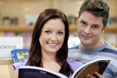 Portrait of a cute couple reading a book in a shop Royalty Free Stock Image