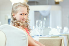 Portrait of cute curly girl posing at table Royalty Free Stock Image