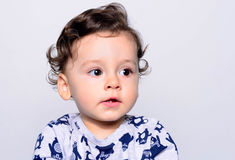 Portrait of a cute curly hair baby boy looking away. Royalty Free Stock Photos