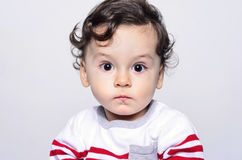 Portrait of a cute curly hair baby boy looking surprised. Stock Photo