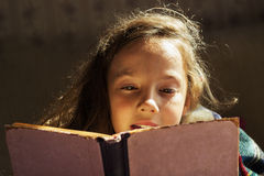 Portrait of cute curly school girl reading a book in cold day Royalty Free Stock Photos