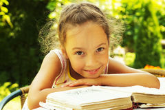 portrait of cute curly school girl reading an old book outside Royalty Free Stock Image