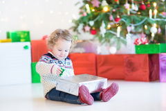 Portrait of a cute curly toddler girl opening her Christmas present Stock Image