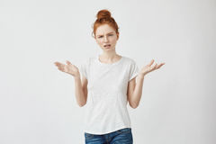 Portrait of cute displeased redhead girl gesturing looking at camera. Isolated on white background. Royalty Free Stock Photography