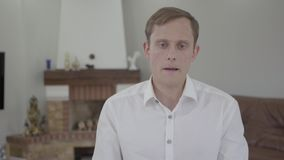 Portrait of cute emotional blond man with amazing gray eyes in white t-shirt talking looking into the camera in the room. Portrait of a handsome emotional blond stock video footage