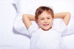 Portrait of a cute emotional little boy in bed Stock Photography