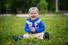 Portrait of a cute European boy on a green lawn with dandelions royalty free stock photo