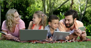Portrait of cute family are lying on the grass and using electronic devices stock video footage