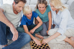 Portrait of a cute family playing chess royalty free stock photos