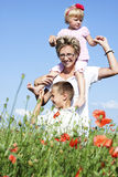 Portrait of cute family in poppy field Royalty Free Stock Images