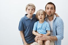 Portrait of cute family of sons and father, hugging and standing surprised over gray background, dropping jaw, seing Stock Image
