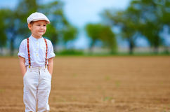 Portrait of cute farmer boy on spring field Stock Photo