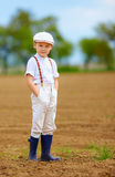 Portrait of cute farmer boy on spring field Royalty Free Stock Image