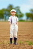 Portrait of cute farmer boy on spring field Royalty Free Stock Photography