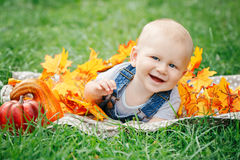 Portrait of cute funny adorable blond Caucasian baby boy with blue eyes in tshirt and jeans romper lying on grass field meadow Royalty Free Stock Photo