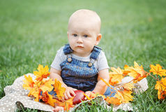 Portrait of cute funny adorable blond Caucasian baby boy with blue eyes in tshirt and jeans romper sitting on grass field meadow Stock Photo