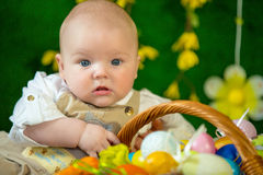 Portrait of a cute funny baby with an easter basket of eggs Royalty Free Stock Image