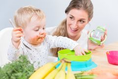 Portrait of a cute baby sitting on high chair while eating solid food royalty free stock photo