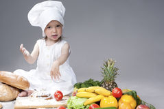 Portrait of Cute Funny Caucasian Female Cook with Lots of Vegetables In Front. Against Gray Background. Horizontal Shot Stock Photography
