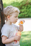 Portrait of cute funny little blond Caucasian child girl toddler standing in the green forest field meadow blowing soap bubbles Stock Photos