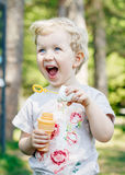 Portrait of cute funny little blond Caucasian child girl toddler standing in the green forest field meadow blowing soap bubbles Royalty Free Stock Photo
