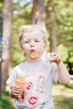 Portrait of cute funny little blond Caucasian child girl toddler standing in the green forest field meadow blowing soap bubbles Stock Images