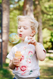 Portrait of cute funny little blond Caucasian child girl toddler standing in the green forest field meadow blowing soap bubbles Stock Image