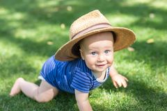 Portrait cute funny little boy in big straw hat having fun on green grass lawn at park. Sweet little baby crawling and smiling at. Garden on bright summer day stock photos