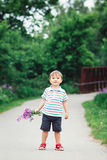 Portrait of a cute funny little boy toddler standing in the forest field meadow with dandelion flowers in hands Royalty Free Stock Photography
