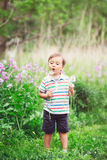 Portrait of a cute funny little boy toddler standing in the forest field meadow with dandelion flowers in hands. And blowing them on a bright summer day, summer Royalty Free Stock Images