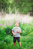 Portrait of a cute funny little boy toddler standing in the forest field meadow with dandelion flowers in hands. And blowing them on a bright summer day, summer Royalty Free Stock Photo